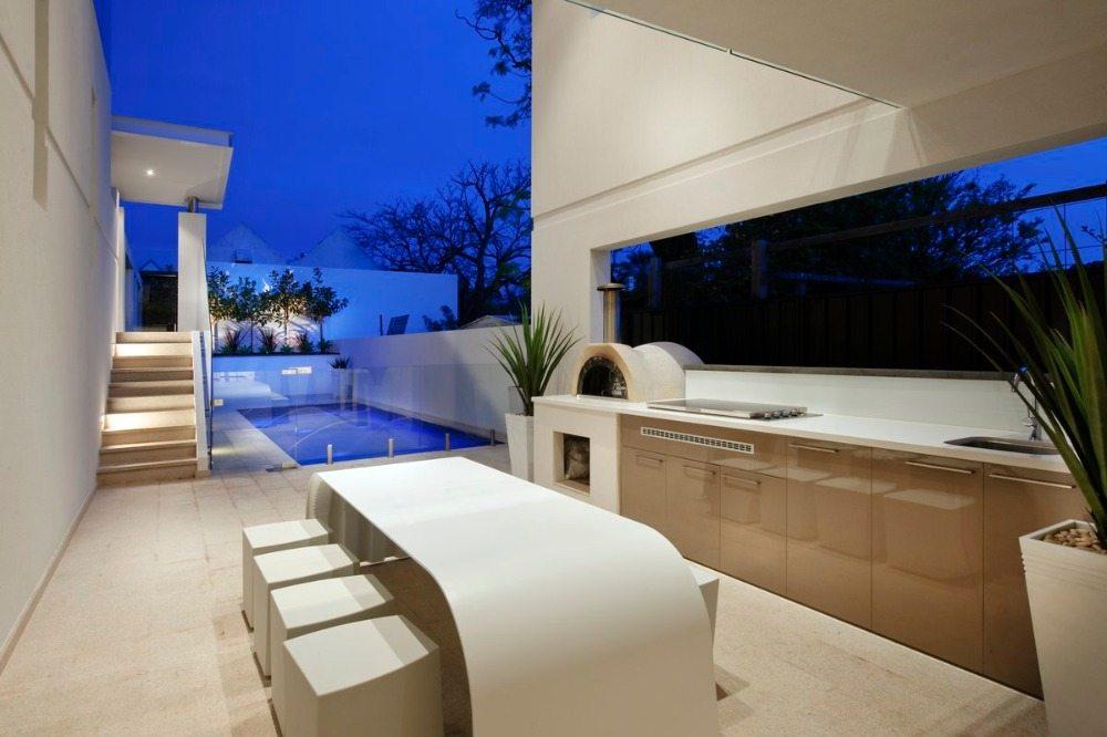 luxuriöse kücheneinrichtung in beige mit pizzaofen und designer tisch in weiß neben pool